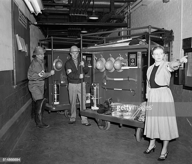 Air raid warden Norma Solberg directs firefighters John McClosky and John McGrath during an air raid drill