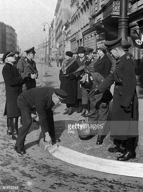 Air raid wardens and police whitewashing kerbs in preparation for an air raid blackout exercise in Berlin scheduled for 19th March 1935