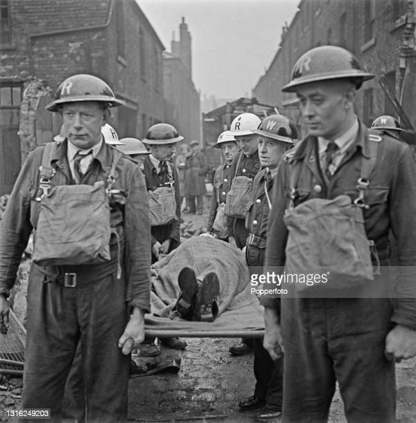 Air Raid Wardens carry a female casualty on a stretcher to be treated in a Ministry of Health Emergency Blood Transfusion Service mobile unit after...