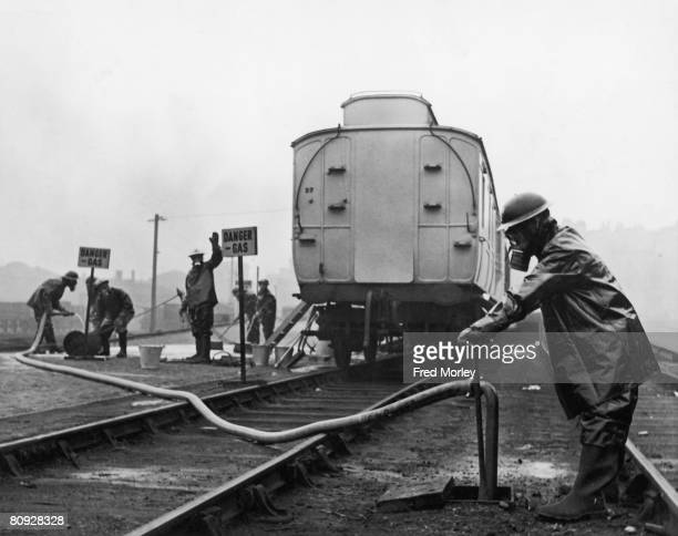 Air raid wardens operating the water supply to a gas decontamination coach operating on the Great Western Railway , 10th February 1941.