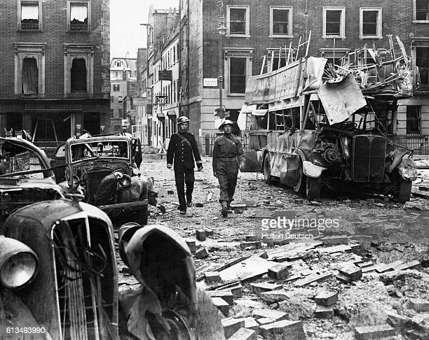 Air raid wardens walk through bombed out buses and automobiles in the aftermath of an air raid on Marble Arch London 1940