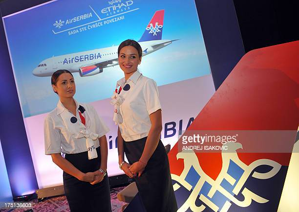 Air Serbia flight attendants pose in front of a picture of an Air Serbia airplane during a presentation in Belgrade on August 1 2013 Abu Dhabibased...