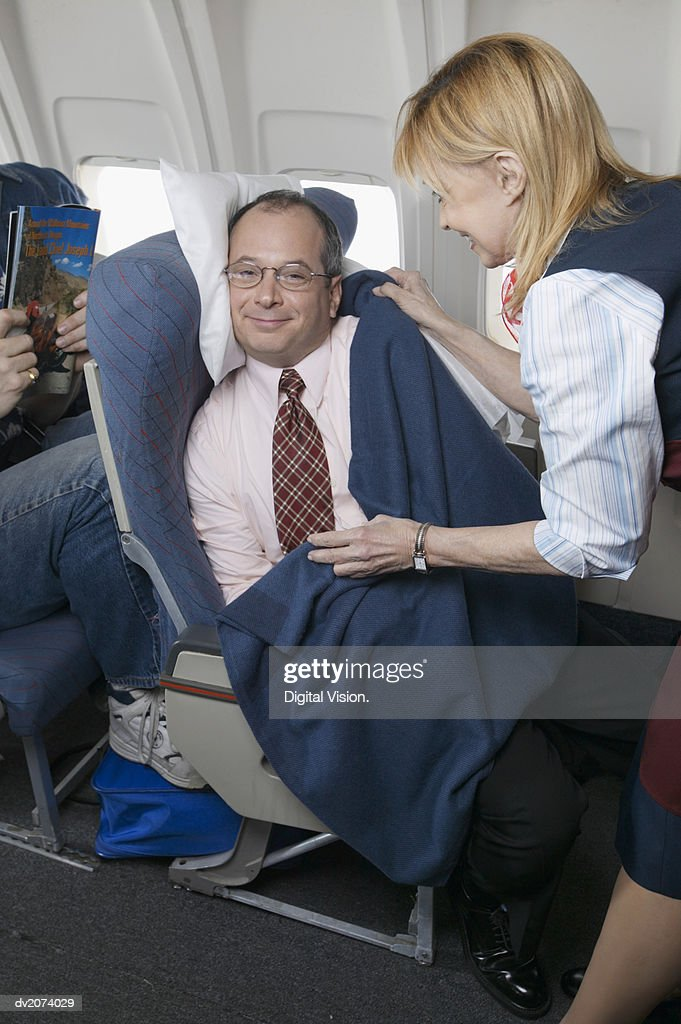Air Stewardess Adjusting a Businessman's Blanket During a Flight : Stock Photo