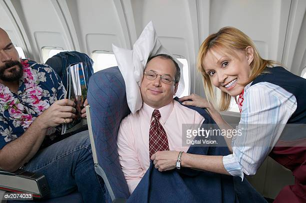 Air Stewardess Adjusting a Businessman's Blanket During a Flight