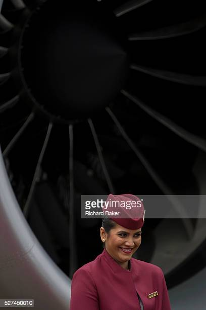 Air stewardess and engine turbofan blades of a Qatar Airways Boeing 787 at the Farnborough Air Show UK The lady smiles with the large turbofans of...