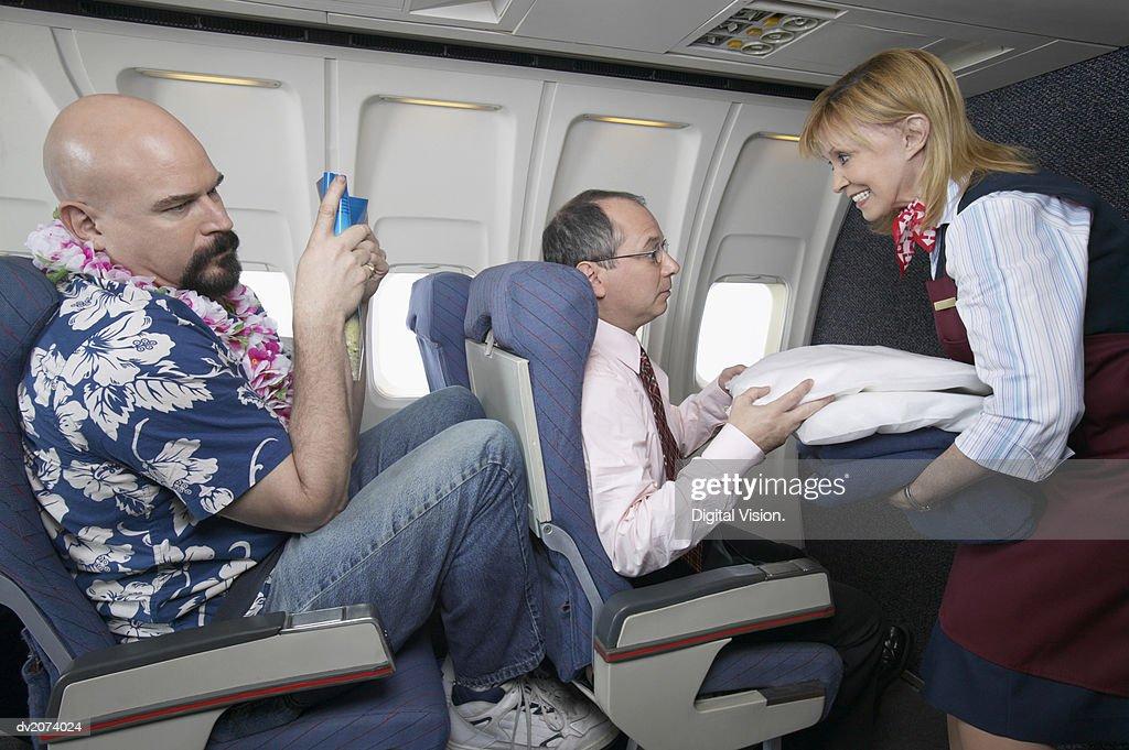 Air Stewardess Giving a Businessman a Pillow During a Flight : Stock Photo