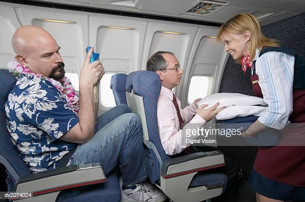 Air Stewardess Giving a Businessman a Pillow During a Flight
