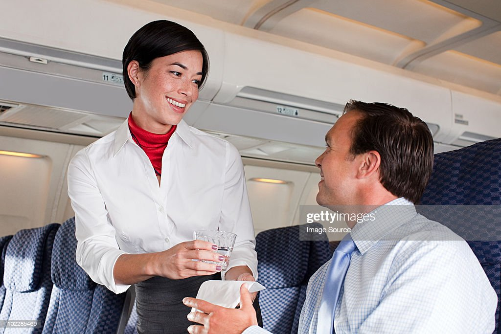 Air stewardess giving drink to passenger : Stock Photo