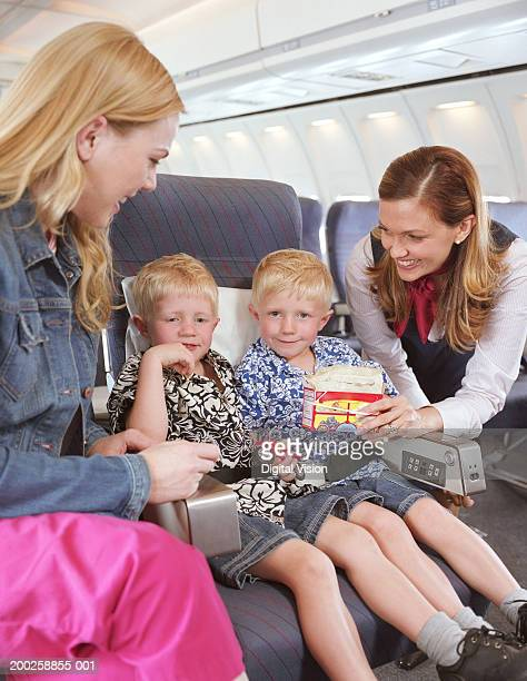 Air stewardess offering snack to twin boys (3-5) smiling