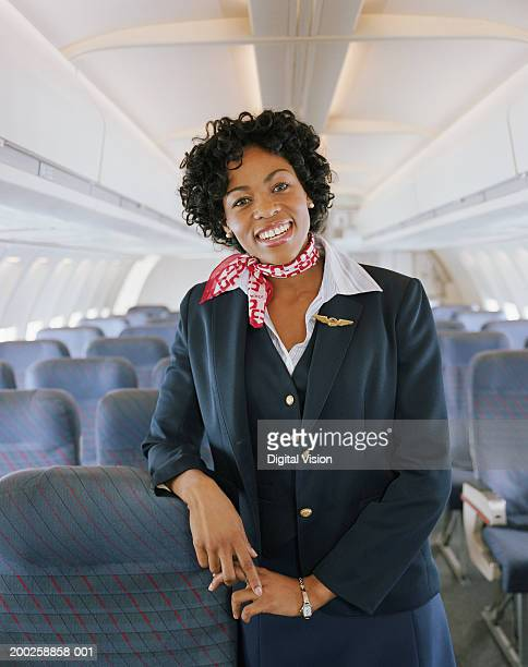 Air stewardess on aeroplane, smiling, portrait