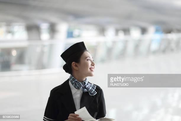 Air stewardess reading book in airport