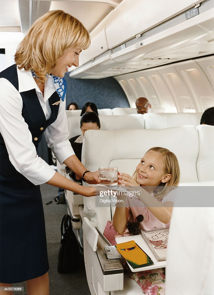 Air Stewardess Serving a Drink to a Girl in an Aircraft Cabin : Stock Photo