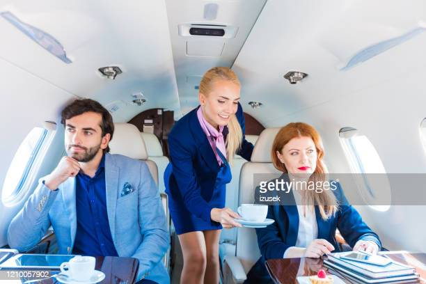 air stewardess serving coffee in corporate jet - izusek stock pictures, royalty-free photos & images