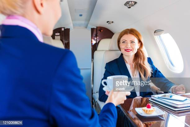 air stewardess serving coffee in corporate jet - air vehicle stock pictures, royalty-free photos & images