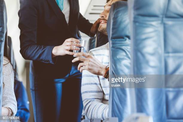 Air stewardess serving water inside an airplane