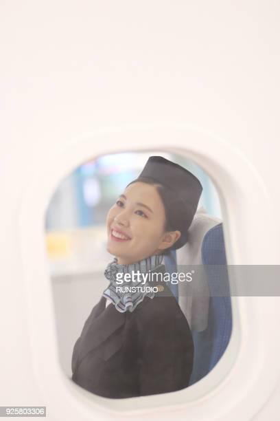 Air stewardess sitting on airplane