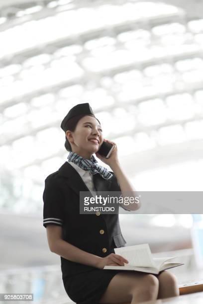 Air stewardess talking on smartphone in airport