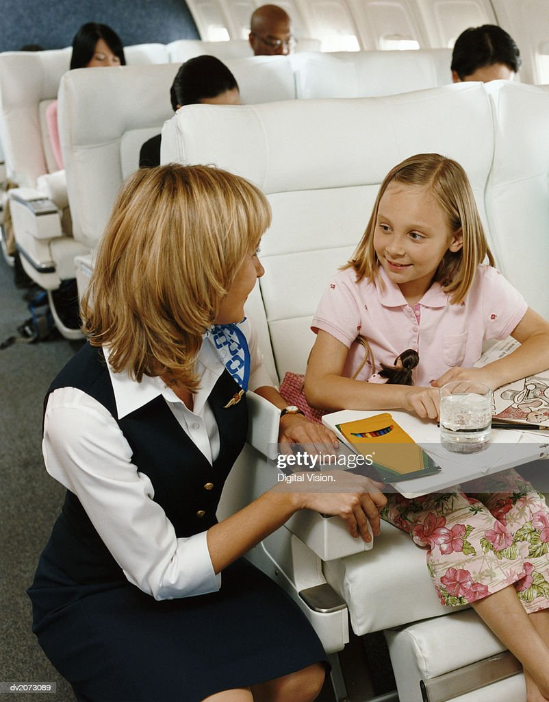 Air Stewardess Talking to a Girl in an Aircraft Cabin : Stock Photo