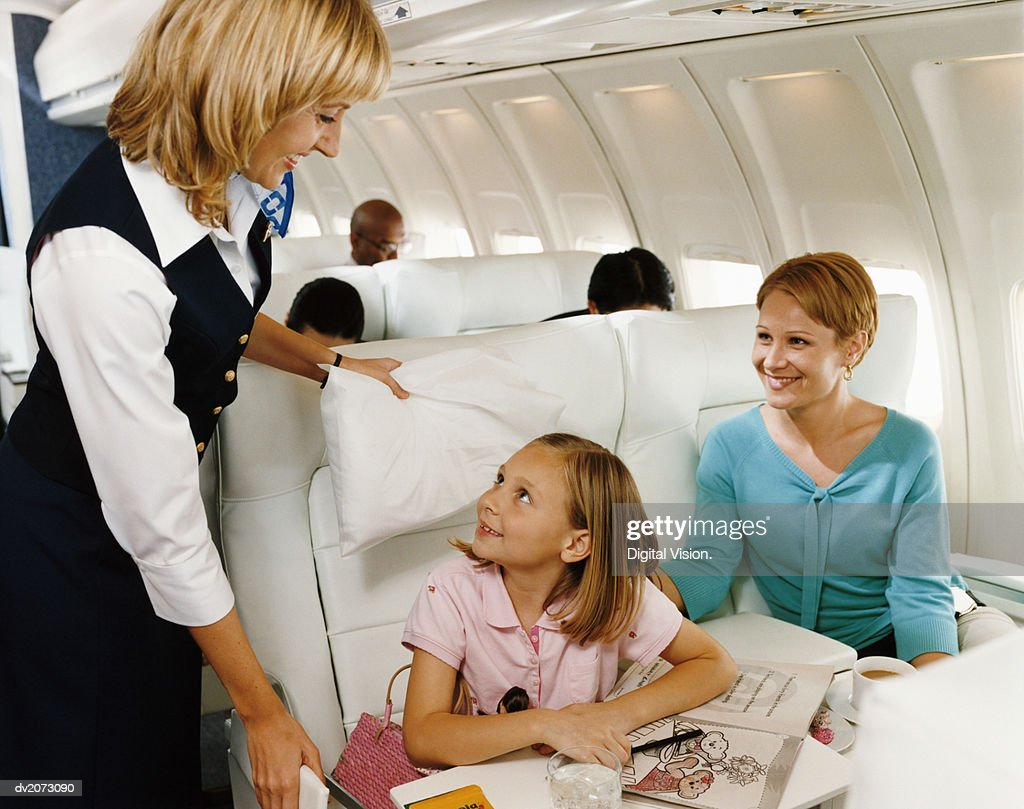 Air Stewardess Talking to Mother and Daughter in an Aircraft Cabin Interior : Stock Photo