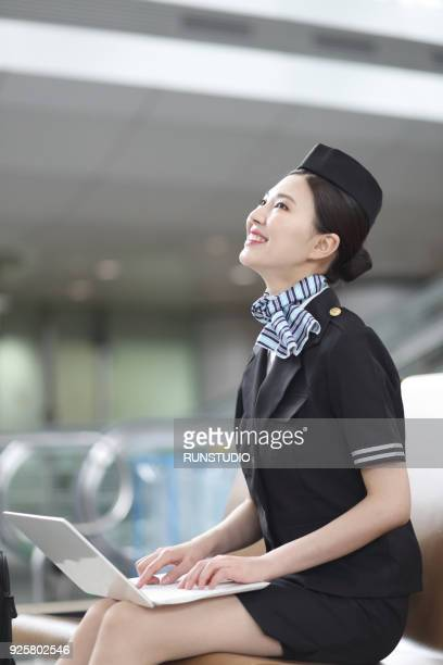 Air stewardess using laptop in airport
