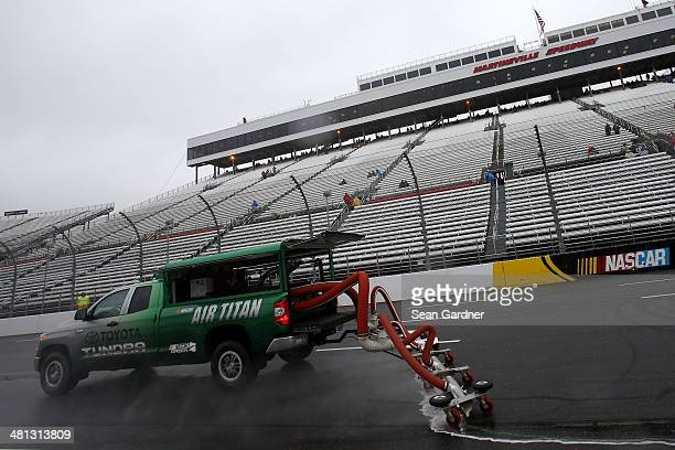 Air Titan 2.0 trucks work to dry the track during a rain delay for the NASCAR Camping World Truck Series Kroger 250 at Martinsville Speedway on March...