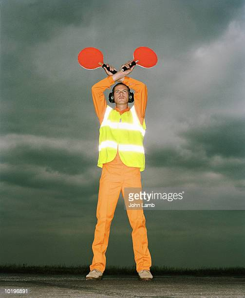 Air traffic control signalman outdoors, arms raised and crossed above