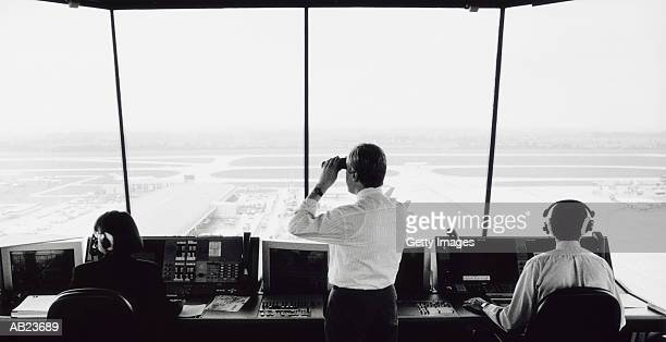 Air traffic control worker in tower viewing runway through binoculars