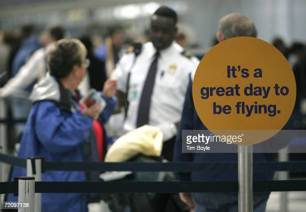 Air travelers speak with a TSA worker behind a sign that reads 'it's a great day to be flying' in Terminal One at O'Hare International Airport...