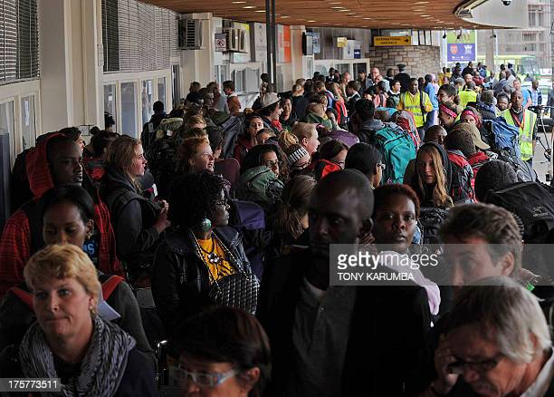 Air travellers queue as they wait to board their flights at Jomo Kenyatta International Airport in Nairobi on August 8 2013 after limited flights...