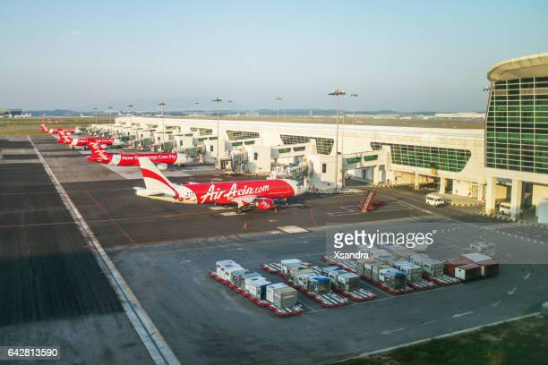 airasia airplanes in kuala lumpur international airport - kuala lumpur international airport stock photos and pictures