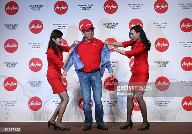 AirAsia Bhd flight attendants take the shirt off Yoshinori Odagiri chief executive officer of AirAsia Japan to show the company's uniform underneath...
