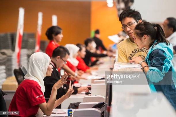 AirAsia Bhd ground staff serve customers checking in for their flights at Kuala Lumpur International Airport 2 in Sepang Malaysia on Tuesday June 24...