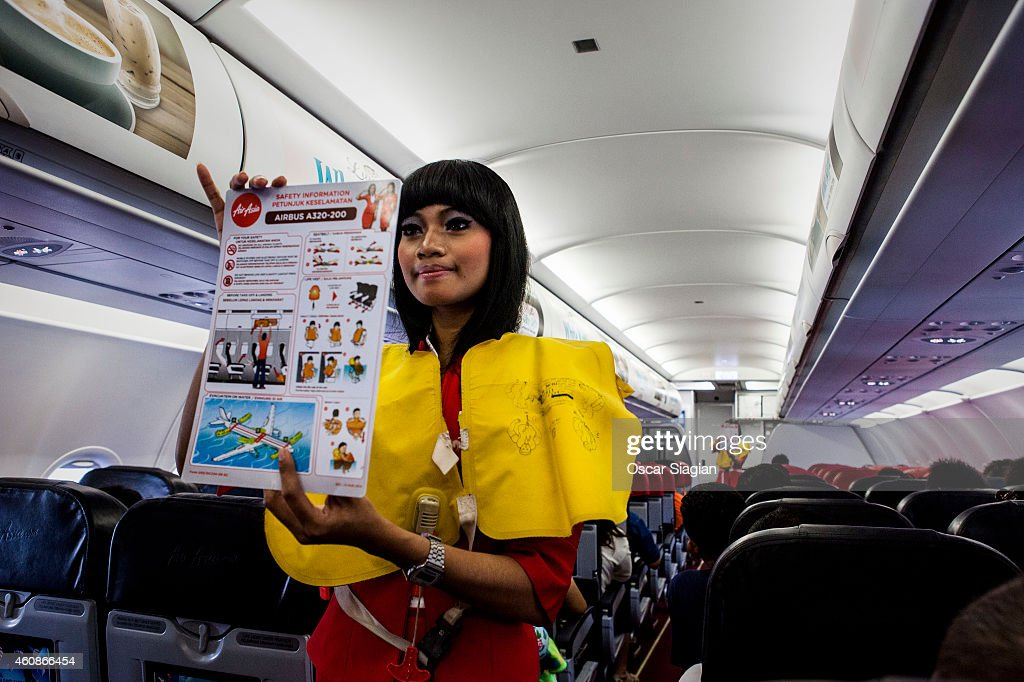 AirAsia stewardess show the safety flight information inside the cabin for preparation before take off at Soekarno Hatta International Airport on December 28, 2014 in Jakarta, Indonesia. AirAsia announced that flight QZ8501 from Surabaya to Singapore, with 162 people on board, lost contact with air traffic control at 07:24 a.m. Sunday local time.