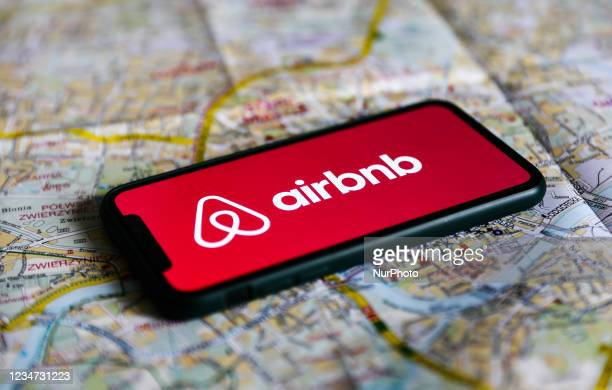 Airbnb logo displayed on a phone screen and a map of Krakow are seen in this illustration photo taken in Krakow, Poland on August 17, 2021.
