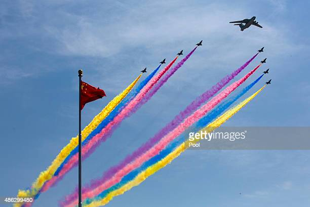 Airborne early warning and control system leads J-10 fighter jets flying past a national flag during a military parade to mark the 70th anniversary...