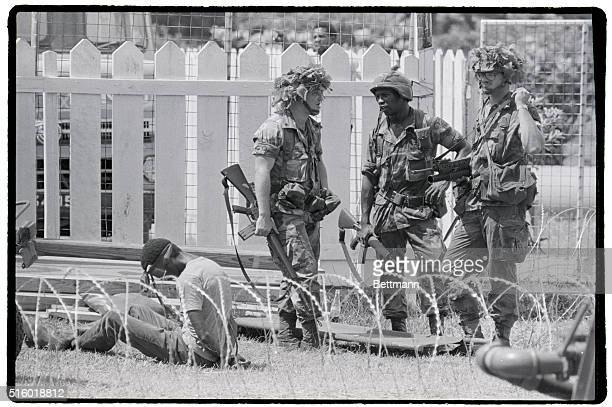 US Airborne troops guard a bound and blindfolded prisoner about to be transported by helicopter at Pearls Airport during the Grenada Invasion |...