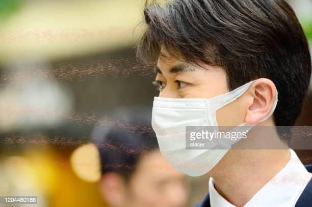 virus aerotransportado y hombre en traje usando máscara facial - coronavirus fotografías e imágenes de stock