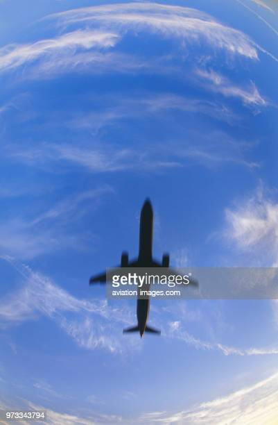 Airbus A321200 on finalapproach with clouds behind motionblurred image