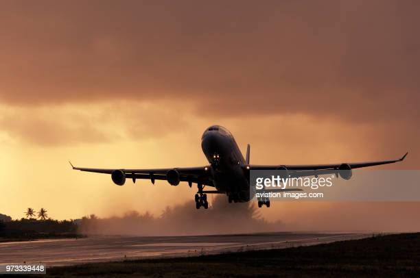 Airbus A340313X takeoff at dusk from a rainy wet runway with the engine exhaust making water spray