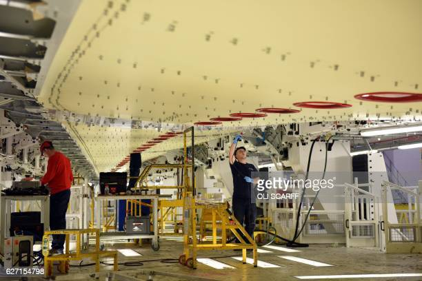Airbus employees construct a wing for an Airbus A350 aircraft at Airbus' wing production plant near Broughton in northeast Wales on December 1 2016...