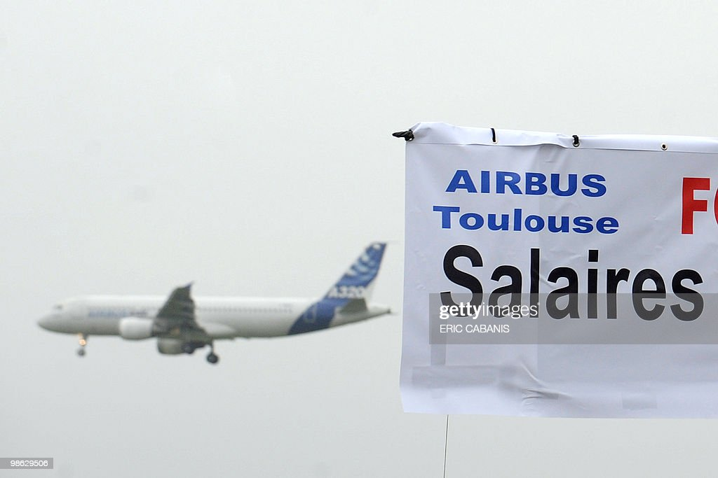 A Airbus takes off as European aircraft manufacturer Airbus employees demonstrate on April 23, 2010 in Toulouse, southwestern France, in front of the entrance of their company to ask for better rise of their wage. Banner reads 'Airbus Toulouse, Wages'.