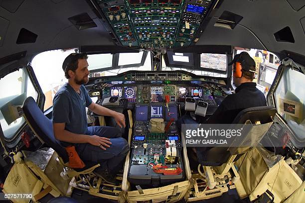 Airbus technicians work inside an A380 cockpit during its assembly in Blagnac on April 22 2016 The A380 is an Airbus double deck long haul fourengine...