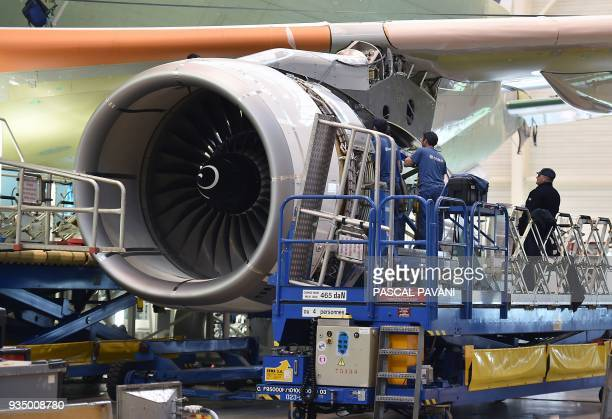 Airbus technicians work on a RollsRoyce Trent 700 aircraft engine on the assembly line of the Airbus Beluga XL large transport aircraft on March 20...