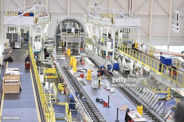 Airbus technicians work on the assembly line of the Airbus Beluga XL large transport aircraft on March 20 2018 in Blagnac near Toulouse southwestern...