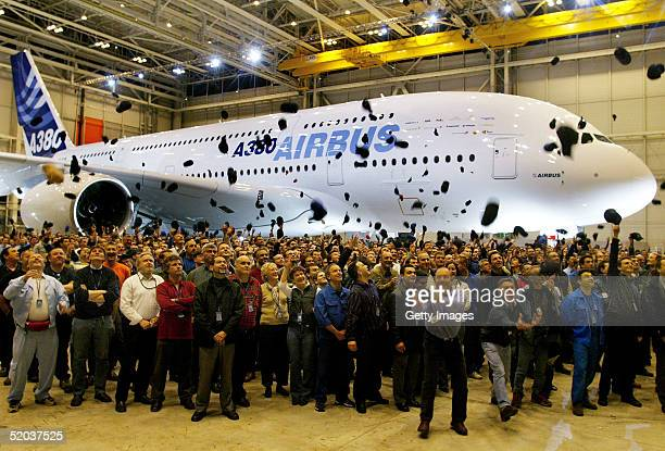 Airbus workers throw hats in the air in front of the new Airbus A380 superjumbo during its unveiling ceremony on January 18 2005 in Toulouse France...