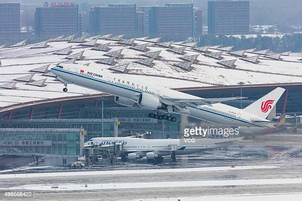 Aircraft are seen at the Beijing Capital International Airport on November 23 2015 in Beijing China Workers cleared the snow at the Beijing Capital...