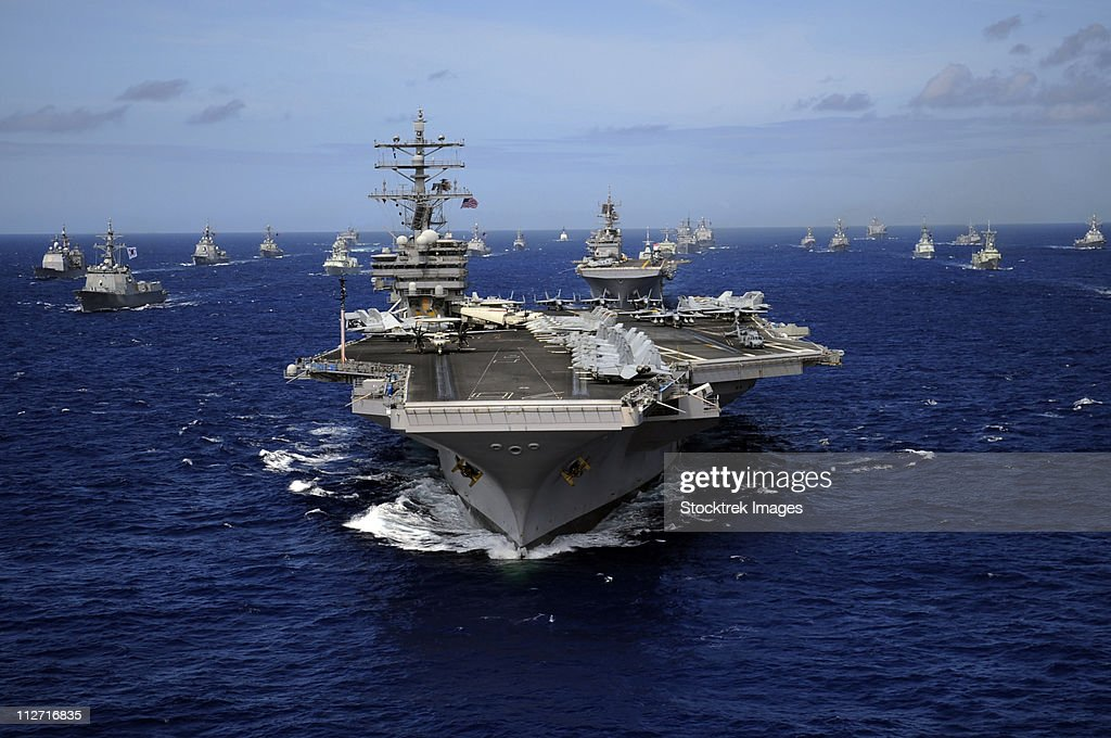 Aircraft carrier USS Ronald Reagan leads a mass formation of ships through the Pacific Ocean. : Stock Photo