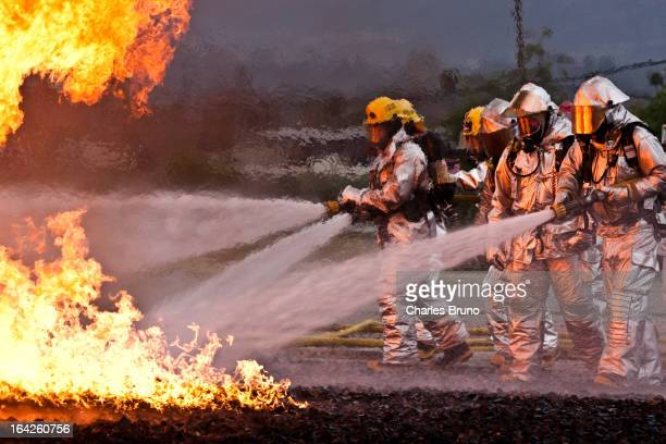 Aircraft Crash Rescue Firefighters attacking the fire with multiple hose lines.