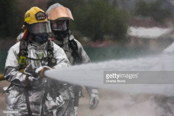 Aircraft Crash Rescue Firefighters discharging a straight stream from hoses and nozzle