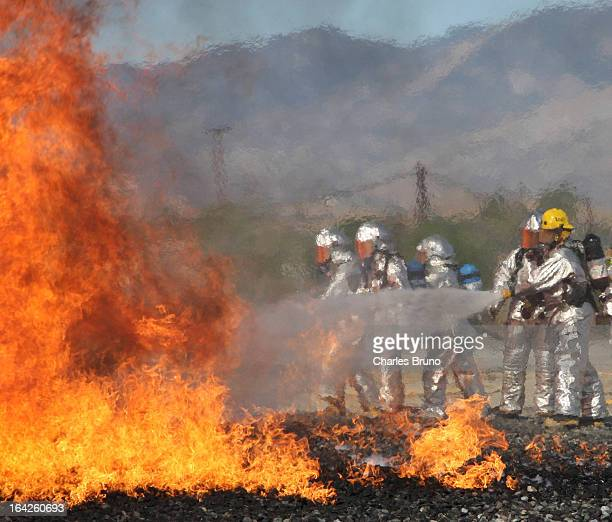 Aircraft Crash Rescue training in Southern California with hoses advancing on the fire.